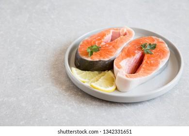 fresh fish. fresh salmon steaks with lemon in a light plate.