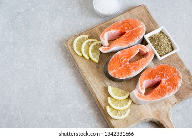 fresh fish. fresh salmon steaks with lemon, spices and salt on a cutting board
