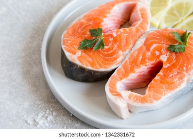 fresh fish. fresh salmon steaks with lemon, spices and salt in a light plate.