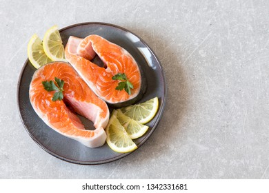 fresh fish. fresh salmon steaks with lemon, spices and salt in a dark plate.
