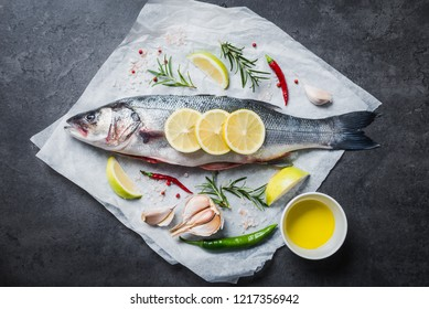 Fresh fish sea bass and ingredients for cooking on black slate table. Top view with copy space.