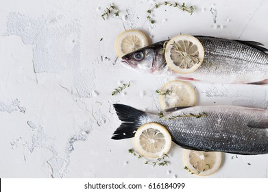 Fresh fish of sea bass on a light background on the ice with slices of lemon and sprigs of thyme, top view