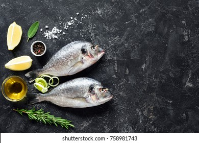 Fresh fish Sea Bream, Herbs, Spices, Olive oil and Cooking ingredients on Stone Slate Background. Top view. Fish ready for cooking. Copy space for your text