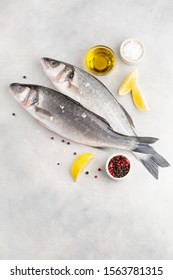 Fresh fish seabass and ingredients for cooking pepper, salt, lemon, olive oil on light grey table. Top view with copy space.
