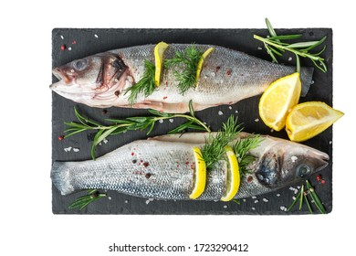 Fresh fish seabass and ingredients for cooking. Raw gutted fish seabass with spices and herbs on black slate isolated on white background. top view