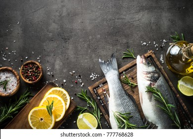 Fresh fish seabass and ingredients for cooking. Raw fish seabass with spices and herbs on black slate background. Top view with copy space.