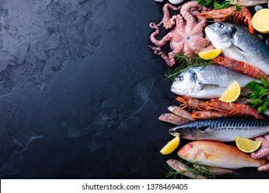 Fresh fish and seafood assortment on black slate background. Top view. Copy space.