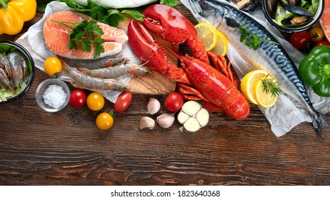 Fresh fish and seafood with herbs, spices and vegetables on rustic wooden background. Balanced diet and cooking concept.Healthy eating. Top view with copy space.
