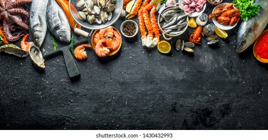 Fresh fish and seafood. On black rustic background