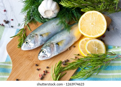 Fresh fish with the vegetables, condiment and lemon, bluefish. Food preparation.
