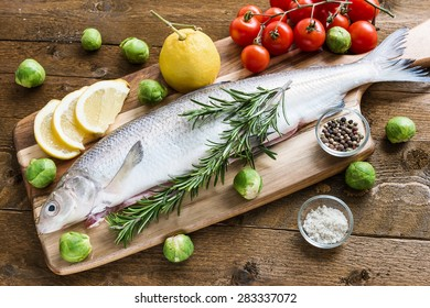 Fresh fish with vegetables on wooden board. Top view