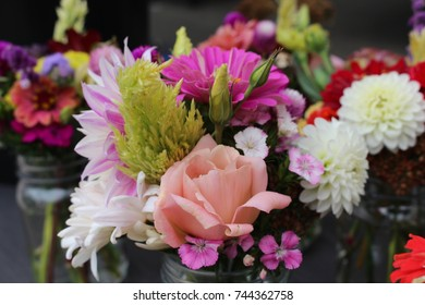 Fresh flower bouquets at farmers market for sale in many colors of purple, green, white, and orange