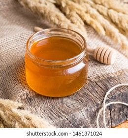 Fresh flower honey in a glass jar. Rustic style. Craft packaging and dried flowers.  Old wooden background and canvas.