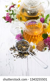 fresh flower honey, tea and ingredients on white background, vertical top view