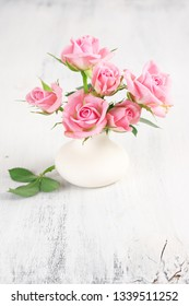 Fresh flowers bouquet of pink roses in ceramic vase on white rustic shabby background.