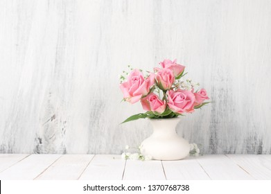 Fresh flowers bouquet of pink roses in ceramic vase on white wood table against rustic shabby wall.