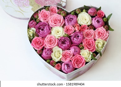 fresh flowers as a gift in the shape of a heart. roses in a box - heart close-up with a blurred background on a white wooden table. pink roses, yellow roses, green