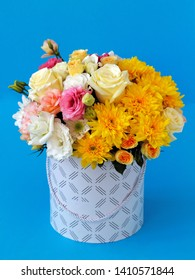 fresh flowers in a hat box, yellow one-headed and Bush rose, yellow chrysanthemums, pink and white eustoma, green close-up on a blue background with a blurred background