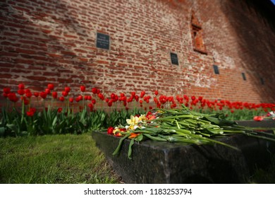 a lot of fresh flowers on the grave, a symbol of memory of the deceased and respect for the deceased person, on the memorial monument on the anniversary of his death in the cemetery brought bouquets