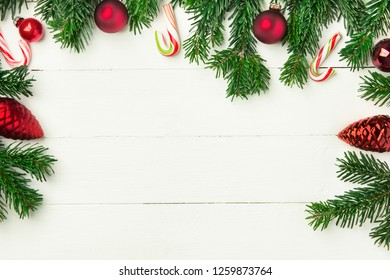 Fresh fluffy fir tree branches red ornament balls candy canes on white plank wood backdrop. Styled Christmas New Year background greeting card poster banner template