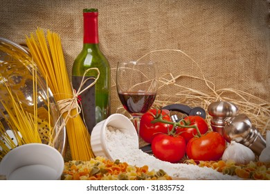 Fresh Food including pasta, tomatoes wine and garlic on a spread ready for eating.