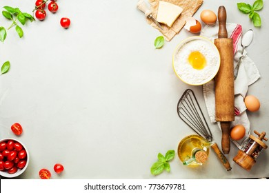 Fresh food ingredients for italian cuisine (Parmigiano, tomato, basil, olive oil, daugh ingredients) on rustic background. Top view