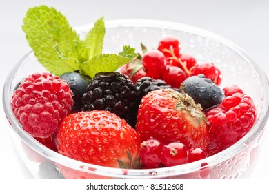 Fresh forest berries in a glass on a white background isolated