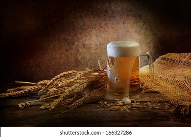 Fresh fragrant foamy beer of light grades in a transparent glass beer mug