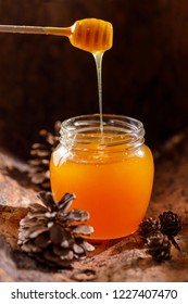 Fresh fragrant honey flowing into a beautiful glass jar with a wooden spoon. Close-up.