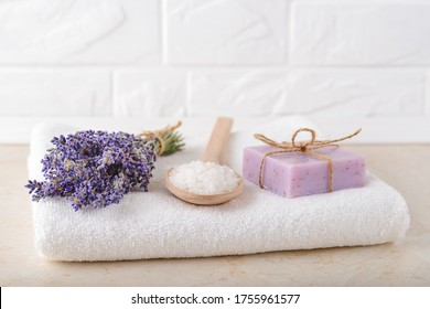 Fresh fragrant lavender, cosmetic bath salt in a wood spoon and lavender soap on a white terry towel in a bathroom. Home made spa, skincare and cosmetology concept. Front view.