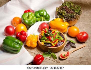 Fresh fragrant salad of colorful peppers with basil leaves and salad on the table