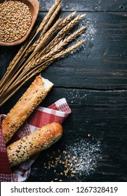 Fresh french baguette bread, organic flour and wholegrain wheat on dark vintage wooden board form above. Top view of traditional baked bread. Bakery shop menu background.