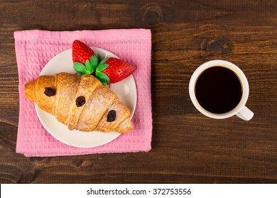 Fresh french croissant and strawberry. cup coffee. wooden table background. Top view
