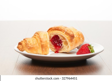 Fresh french croissant with strawberry jam filling cut into two pieces and strawberry on white ceramic plate on bright light brown wooden table background