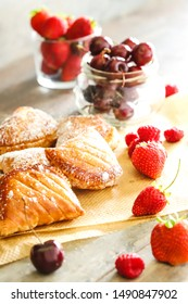 Fresh French pastries with fresh cherries strawberries and raspberries on a baking sheet with icing sugar on the pastries