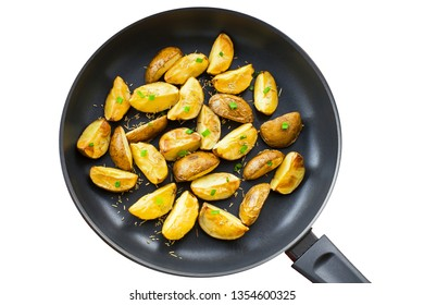 Fresh fried potato wedges with rosemary and spring onion on a pan, isolatedon white background, top view close-up shot