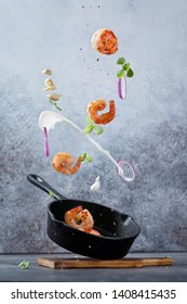 Fresh fried shrimp fly into a pan. Sea food with garlic, onion, cream, spices and basil flying into a pan on modern concrete background. Food preparation, meal ready for cooking.