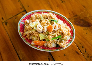 Fresh fried yellow noodle with squid and vegetables. Traditional thai seafood cuisine.