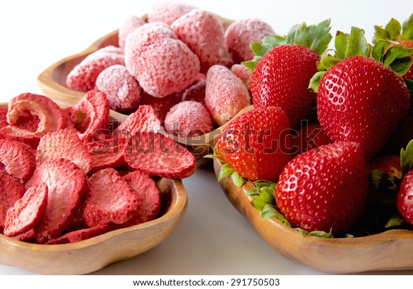 Fresh, frozen and dehydrated strawberry in a wooden bowl isolated