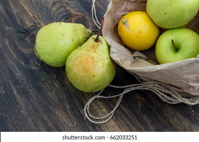Fresh fruit in a craft bag on a dark background. Apple, pear and lemon as ingredients for drinks. Concept of healthy eating.