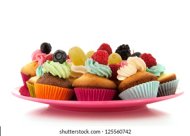 Fresh fruit cupcakes on pink plate  isolated over white background
