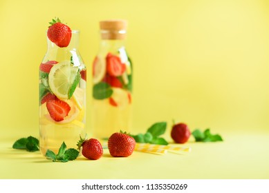 Fresh fruit flavored water with strawberry, lemon, mint on yellow background. Summer drink concept. Copy space. Infused water or citrus lemonade.