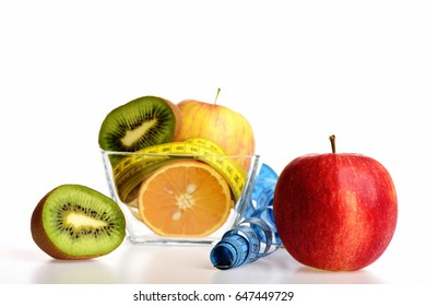 Fresh fruit including yellow apple, halves of kiwi fruit and orange with yellow measure tape in bowl near red apple and roll of blue measure tape isolated on white background. Healthy food concept