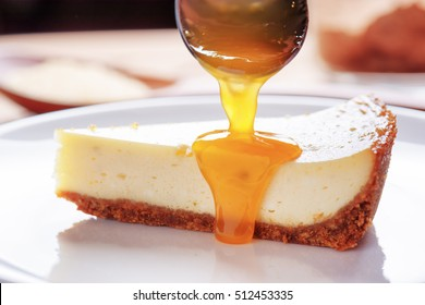 Fresh fruit jam pouring on piece of delicious freshly baked cheesecake on white plate. Topping for sweet dessert.