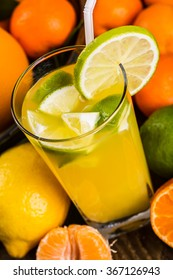 Fresh fruit and juice tangerines with leaves on a wooden table