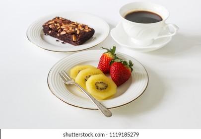 Fresh fruit kiwi, strawberry, black coffee and chocolate brownie on white table.