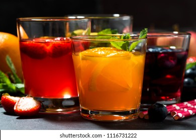 fresh fruit lemonades in assortment on dark table, closeup horizontal