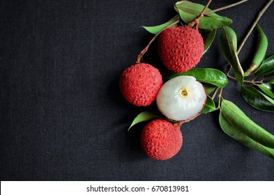 Fresh fruit Lychee on black clothing background, top view photo, copy space for text