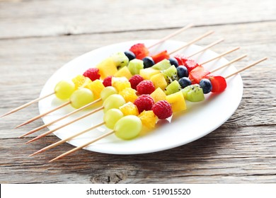 Fresh fruit on skewers on a grey wooden table