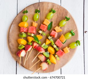 Fresh fruit on sticks on wood